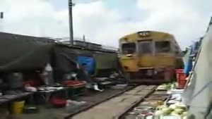 Train Drives Through A Bangkok Market