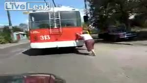 Old Woman Pushes A Broken Trolley Bus