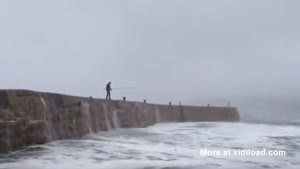 Fisherman Blown Away By Big Wave
