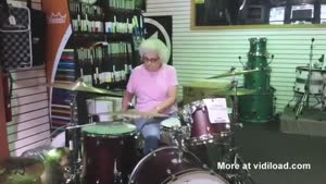 Elderly Woman Playing The Drums In Store