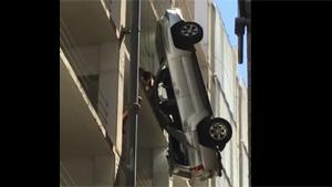 Man Climbing From Dangling Car